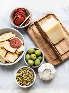 Still life of cutting board and cheese with bowls of crackers, olives, salami and pumpkin seeds, oveの写真素材 [FYI03625912]