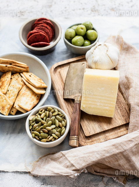 Still life of cutting board and cheese with bowls of crackers, olives, salami and pumpkin seeds, oveの写真素材 [FYI03625915]