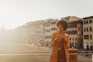 Young woman with afro hair having hot drink, using smartphone in city, Florence, Toscana, Italyの写真素材 [FYI03625994]