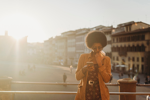 Young woman with afro hair having hot drink, using smartphone in city, Florence, Toscana, Italyの写真素材 [FYI03625998]