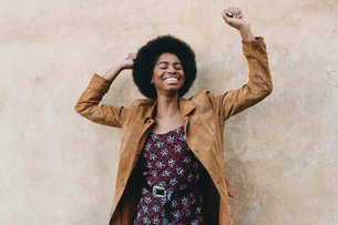 Young woman with afro hair feeling excited against stone wallの写真素材 [FYI03626012]
