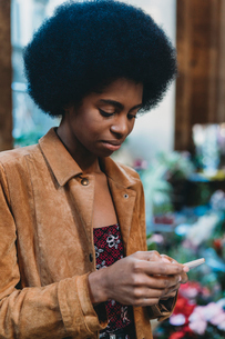 Young woman with afro hair using smartphone in cityの写真素材 [FYI03626039]