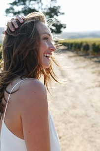 Woman laughing in sunshine in vineyard, Cape Town, South Africaの写真素材 [FYI03626085]