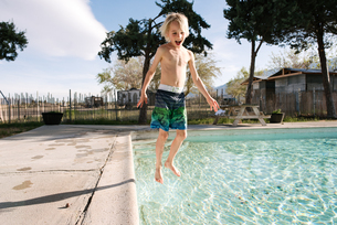 Boy jumping into swimming pool, Olancha, California, USの写真素材 [FYI03626236]
