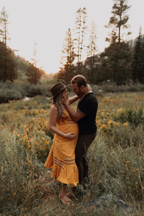 Property Released (PR)egnant mid adult couple hugging amongst wildflowers at sunset in rural valley,の写真素材 [FYI03626252]