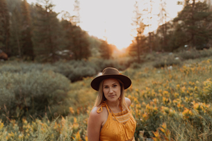 Mid adult woman in felt hat amongst wildflowers at sunset in rural valley, portrait, Mineral King, Cの写真素材 [FYI03626254]