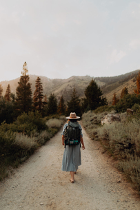 Young woman in maxi dress wearing backpack walking along rural road, rear view, Mineral King, Califoの写真素材 [FYI03626258]