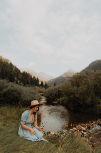 Young woman sitting picking wildflowers by rural river, Mineral King, California, USAの写真素材 [FYI03626286]