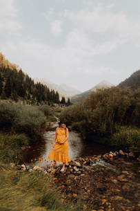 Property Released (PR)egnant woman in orange maxi dress crossing stepping stones in rural river, Minの写真素材 [FYI03626290]