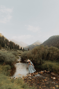 Young woman in stetson crossing stepping stones in rural river, Mineral King, California, USAの写真素材 [FYI03626292]