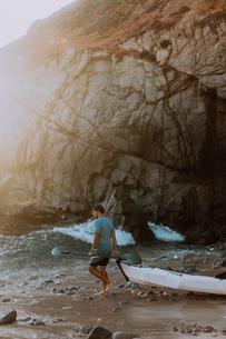 Man dragging kayak into sea, Big Sur, California, United Statesの写真素材 [FYI03626426]