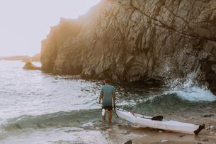 Man dragging kayak into sea, Big Sur, California, United Statesの写真素材 [FYI03626427]