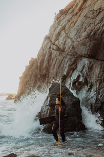Woman with flippers and spear on beach, Big Sur, California, United Statesの写真素材 [FYI03626433]