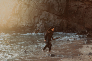 Woman with flippers and speargun on beach, Big Sur, California, United Statesの写真素材 [FYI03626435]