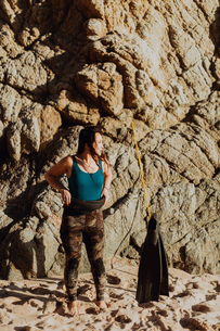 Woman with flippers on beach, rock face in background, Big Sur, California, United Statesの写真素材 [FYI03626447]
