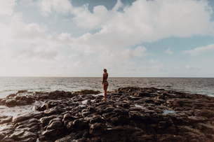 Swimmer standing on rocks by sea, Property Released (PR)inceville, Hawaii, USの写真素材 [FYI03626586]