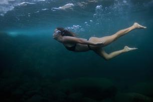 Woman swimming underwaterの写真素材 [FYI03626599]