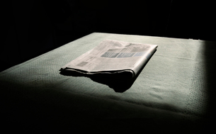 A newspaper folded, waiting to be read in morning light, low keyの写真素材 [FYI03626638]
