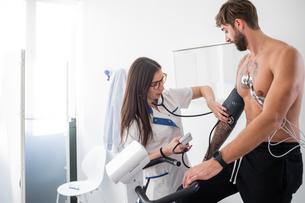Nurse performing ECG test on patient in consultation roomの写真素材 [FYI03626699]