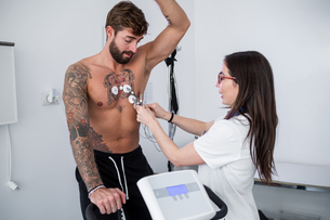 Nurse performing ECG test on patient in consultation roomの写真素材 [FYI03626704]