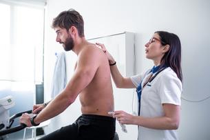 Nurse performing ECG test on patient in consultation roomの写真素材 [FYI03626707]
