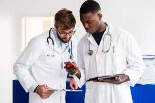 Doctors using smartphone at hospital receptionの写真素材 [FYI03626737]