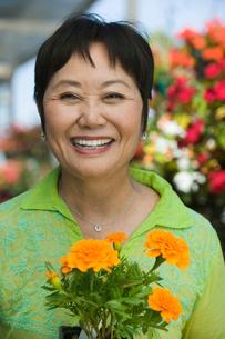 Woman Holding Flowers in plant nursery  portraitの写真素材 [FYI03626827]