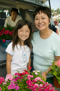 Grandmother and granddaughter with flowers by back of SUVの写真素材 [FYI03626833]