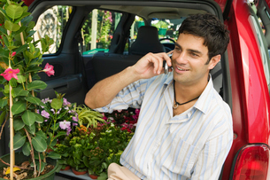 Man sitting by flowers on back of minivan using cell phoneの写真素材 [FYI03626845]