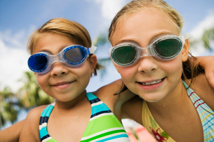Two girls (7-9) wearing swim goggles  portrait.の写真素材 [FYI03626854]