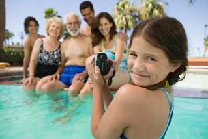 Girl (10-12) in swimming pool  video taping brother (13-15の写真素材 [FYI03626861]