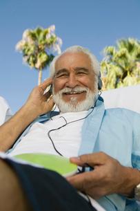 Senior Man sitting outdoors  listening to headphones  lowの写真素材 [FYI03626874]