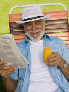 Senior Man sitting on Lawn Chair holding Newspaper and Oraの写真素材 [FYI03626875]