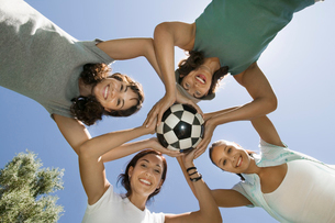 Four women holding soccer ball together  view from below.の写真素材 [FYI03626879]