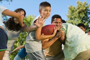 Boy (13-15) playing football with family.の写真素材 [FYI03626880]