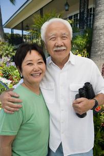 Senior couple with binoculars  outdoors  (portrait)の写真素材 [FYI03626891]