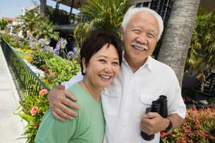 Senior couple with binoculars  smiling  outdoors  (portraiの写真素材 [FYI03626892]