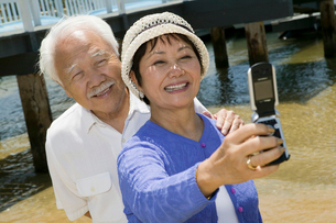 Senior couple photographing themselves by pierの写真素材 [FYI03626894]