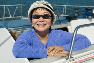 Woman wearing sunglasses on sailboat  smiling  (portrait)の写真素材 [FYI03626897]
