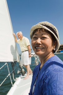 Woman smiling on sailboat  husband in background  (portraiの写真素材 [FYI03626906]