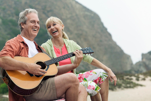 Man playing guitar with wife at beachの写真素材 [FYI03626930]