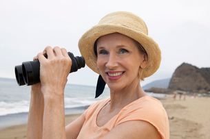 Woman using binoculars at beach  (portrait)の写真素材 [FYI03626940]