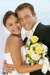 Bride and Groom embracing outdoors  (portrait)の写真素材 [FYI03626950]