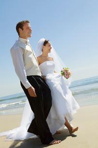 Bride and Groom walking on beachの写真素材 [FYI03626961]
