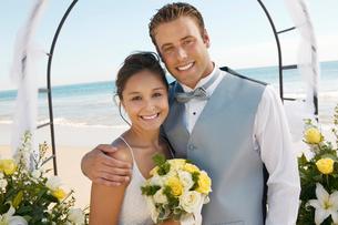 Bride and Groom under archway on beach  (portrait)の写真素材 [FYI03626966]
