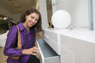 Woman Examining White Dresser drawer in furniture store  pの写真素材 [FYI03626982]