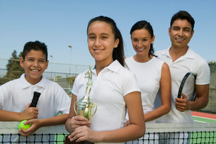Tennis Family on court by net  daughter holding trophy  poの写真素材 [FYI03626989]