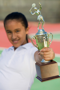 Young girl on tennis court holding trophy  focus on trophyの写真素材 [FYI03626994]
