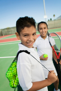 Young boy and girl with tennis equipment on tennis courtの写真素材 [FYI03626995]