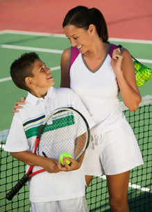 Mother and son by net on tennis court  high angle viewの写真素材 [FYI03627003]